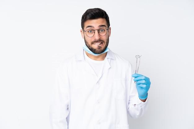 疑いがあると混乱した表情で白い壁にツールを保持している歯科医の男