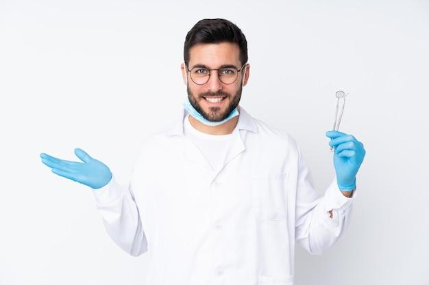 Стоматолог мужчина держит инструменты на белой стене, держа пустое пространство на ладони
