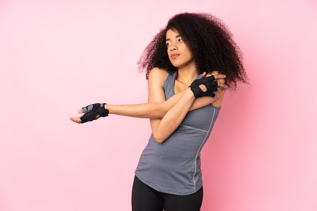 Молодая спортивная женщина на розовом растяжение руки