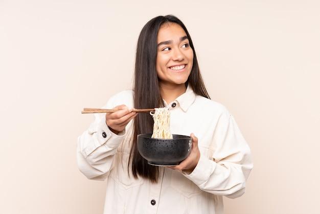 箸で麺のボウルを押しながら見上げるベージュの若い女性