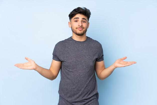 疑問を持つ壁の上のアラビアのハンサムな男