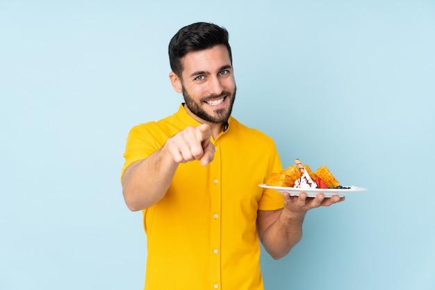 Кавказский мужчина держит вафли на синей стене указывает на вас с уверенным выражением пальца