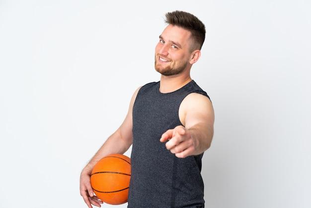 Красивый мужчина на белой стене играет в баскетбол и указывая на фронт