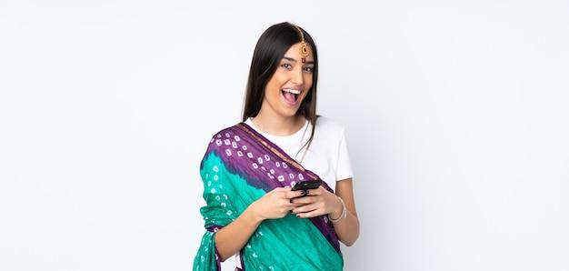 Молодая индийская женщина на белом удивлена и отправив сообщение