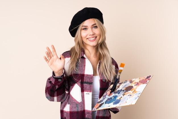 幸せな表情で手で敬礼青い壁にパレットを保持しているティーンエイジャーのアーティストの女の子