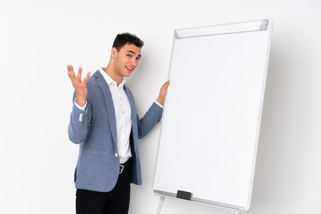Молодой кавказский красивый человек на фиолетовой стене давая представление на белой доске