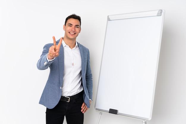 Молодой кавказский красивый человек на фиолетовой стене давая представление на белой доске и показывая знак победы