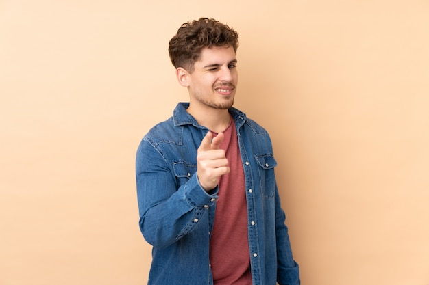 Кавказский мужчина на бежевой стене показывает пальцем на тебя