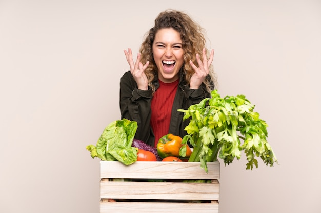不幸で不満と何かに不満のベージュのボックスに摘みたての野菜を持つ農家