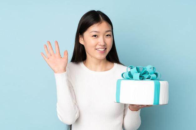幸せな表情で手で敬礼ブルーに大きなケーキを保持しているパティシエ