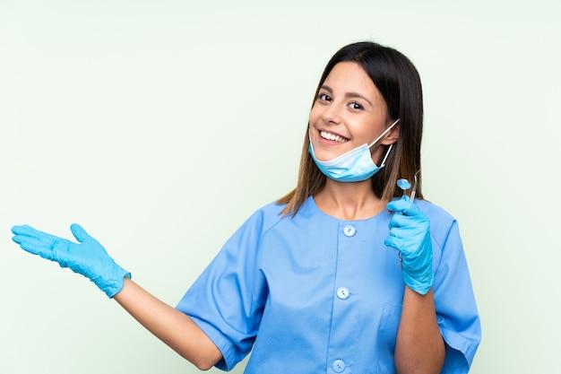 Женщина стоматолог держит инструменты над зеленой стеной, протягивая руки в сторону для приглашения прийти
