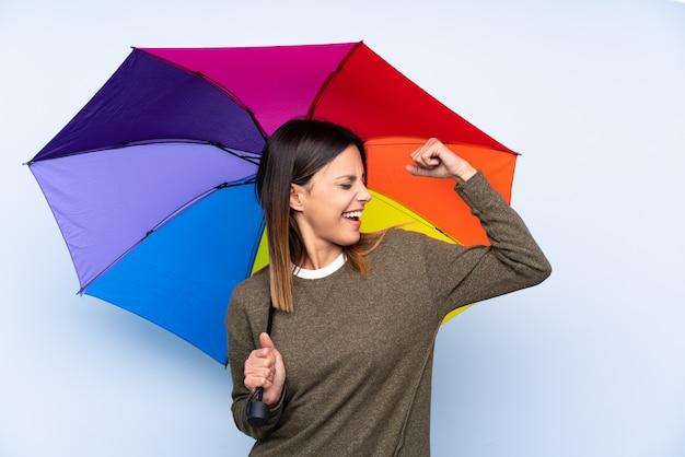 強いジェスチャーを作る青い壁に傘を置く若いブルネットの女性