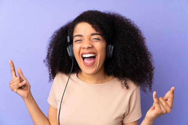 Молодая афро-американская женщина на музыке фиолетовой стены слушая делая жест утеса