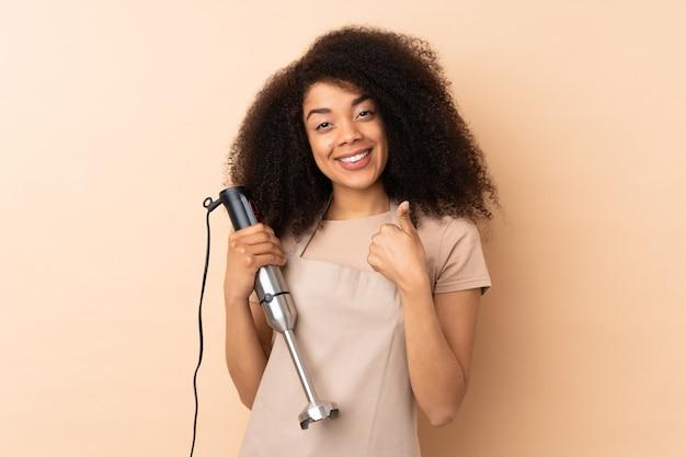 Молодая афро-американская женщина используя ручной блендер на бежевой стене давая жест больших пальцев руки вверх