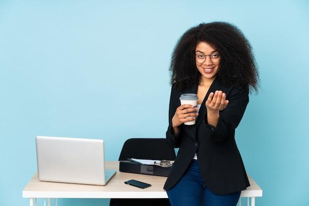 Афро-американская бизнес-леди работая в ее рабочем месте приглашая прийти с рукой.