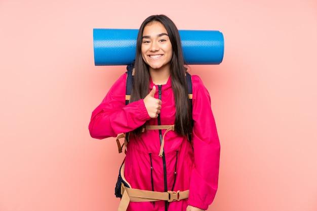 親指ジェスチャーを与えるピンクの壁に大きなバックパックを持つ若い登山家インドの女の子