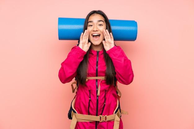 口を大きく開けて叫んでピンクの壁に大きなバックパックを持つ若い登山家インドの女の子