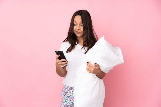 ピンクの壁を考えて、メッセージを送信するパジャマの若い女性