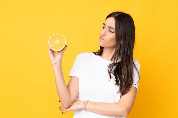 悲しそうな表情で黄色の壁にオレンジを保持している若い白人女性