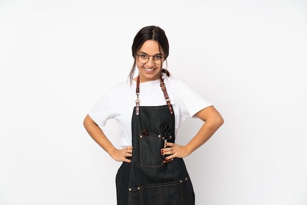 Молодая женщина-парикмахер на белой стене в очках и улыбается