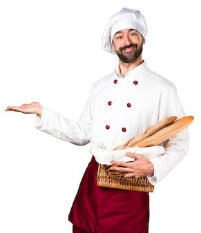 いくつかのパンを持ち、何かを提示している若いパン屋