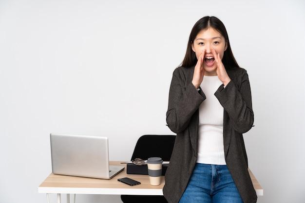 Бизнес азиатская женщина на своем рабочем месте на белой стене, крича и объявив что-то