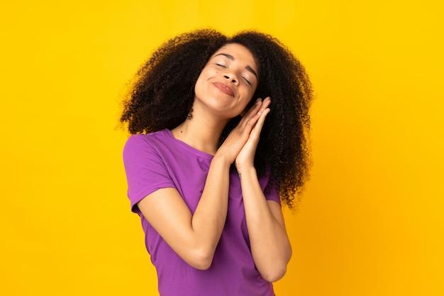 Молодая афро-американская женщина над стеной делая жест сна в прелестном выражении