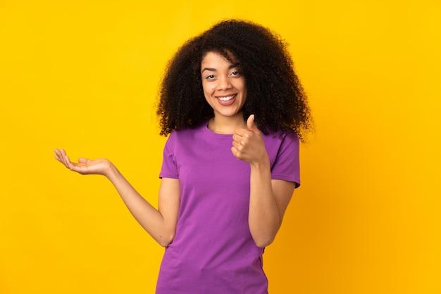 Молодая афро-американская женщина над стеной держа пустое пространство на ладони и с большими пальцами руки вверх
