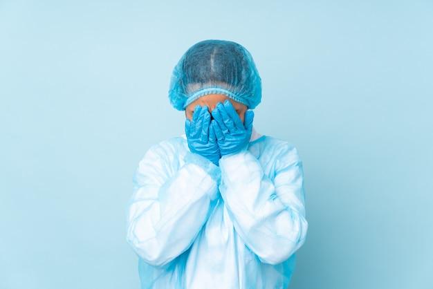 Молодая женщина хирург в синей форме с усталым и больным выражением