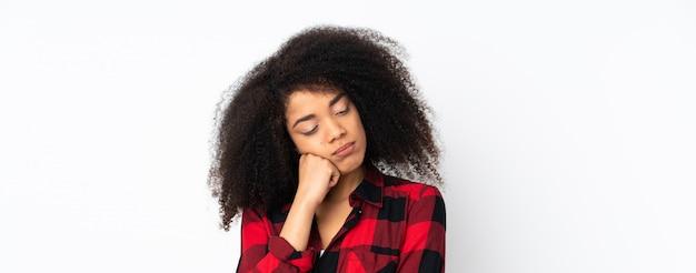疲れて退屈そうな表情で孤立した壁の上の若いアフリカ系アメリカ人女性