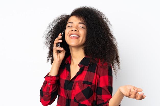 誰かと携帯電話との会話を維持する孤立した壁の上の若いアフリカ系アメリカ人女性
