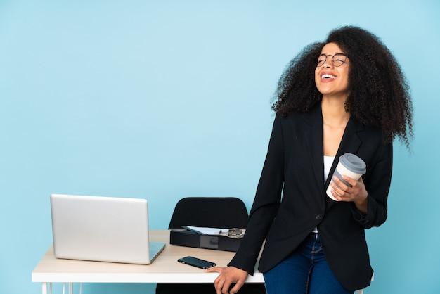 Афро-американская бизнес-леди работая на ее рабочем месте счастливая и усмехаясь