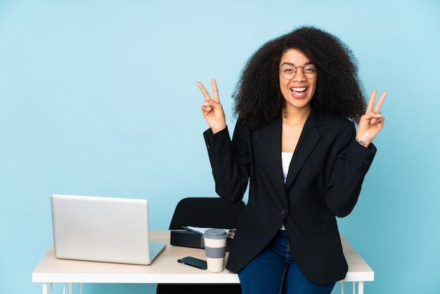 Афро-американская бизнес-леди работая на ее рабочем месте показывая знак победы обеими руками