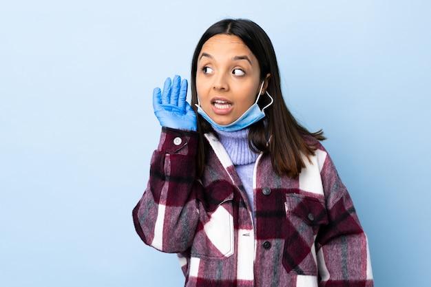 Молодая брюнетка смешанной расы защищает от коронавируса маску и перчатки над изолированной синей стеной, слушая что-то, положив руку на ухо