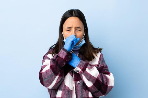 若いブルネットの混血の女性がたくさんの咳青い壁を越えてマスクと手袋でコロナウイルスから保護します。