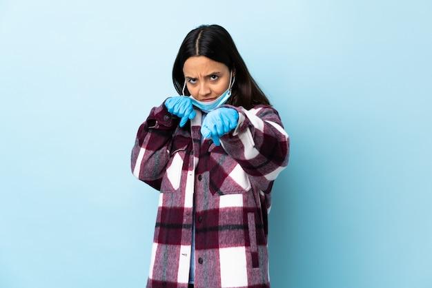 ジェスチャーとの戦いで孤立した青い壁にマスクと手袋でコロナウイルスから保護する若いブルネットの混血女性