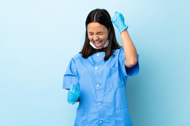 Женщина хирурга над изолированной голубой стеной празднуя победу