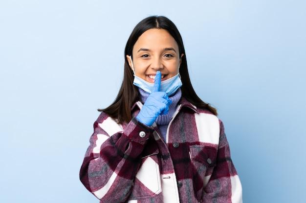 口に指を入れて沈黙ジェスチャーの兆しを見せ分離の青い壁にマスクと手袋でコロナウイルスから保護する若いブルネットの混血の女性