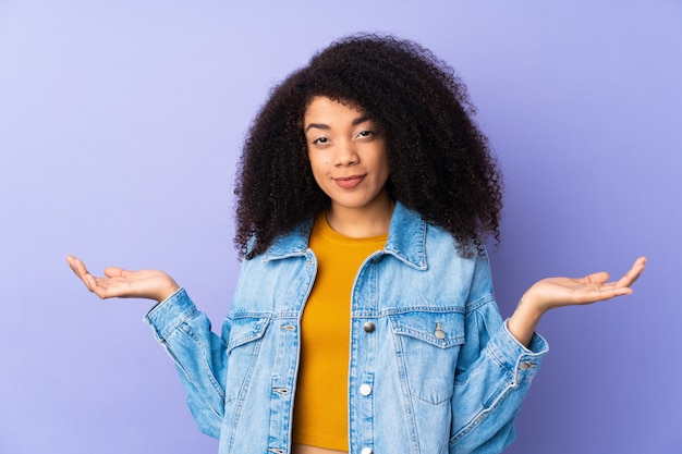 Молодая афро-американская женщина на фиолетовой стене имея сомнения