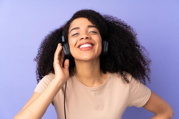 Молодая афро-американская женщина на музыке фиолетовой стены слушая