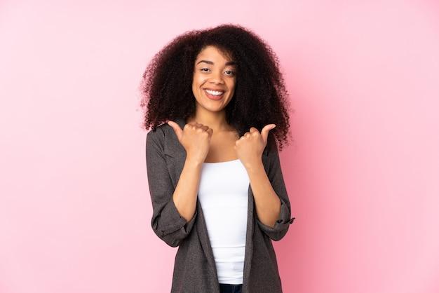 ジェスチャーと笑みを浮かべて親指で壁を越えて若いアフリカ系アメリカ人女性