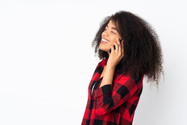 誰かと携帯電話との会話を維持する壁の上の若いアフリカ系アメリカ人女性