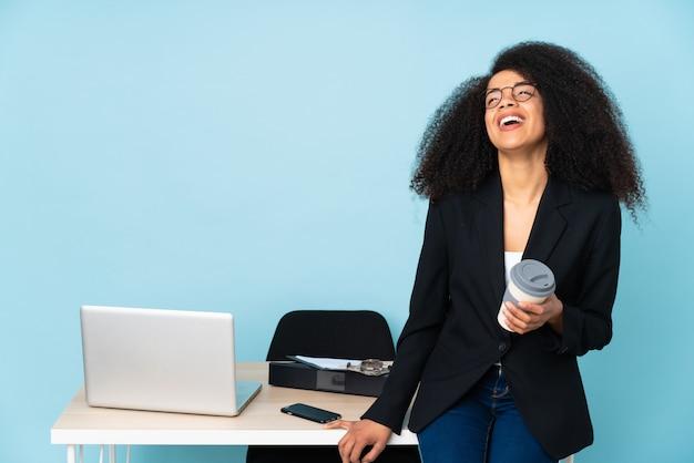 Афро-американская бизнес-леди работая на ее рабочем месте представляя с оружиями на бедре и усмехаться