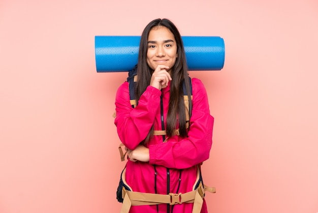 笑っているピンクの壁に大きなバックパックを持つ若い登山家インドの女の子
