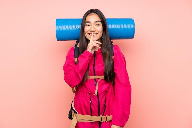 沈黙のジェスチャーをしているピンクの壁に大きなバックパックを持つ若い登山家インドの女の子