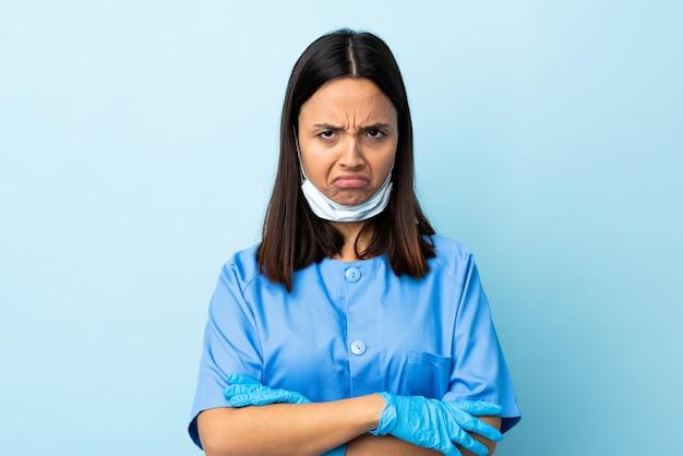 不幸な表情で孤立した青い壁の上の外科医の女性