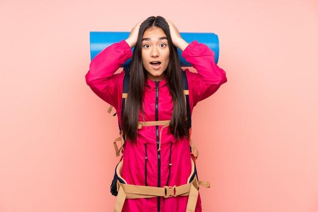 驚いた表情でピンクの壁に大きなバックパックを持つ若い登山家インドの女の子