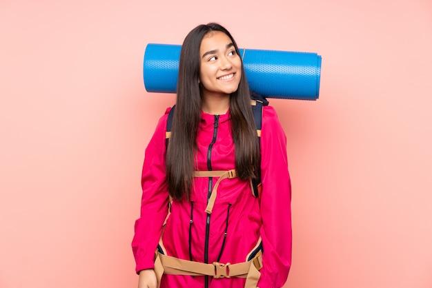 笑って見上げるピンクの壁に大きなバックパックを持つ若い登山家インドの女の子