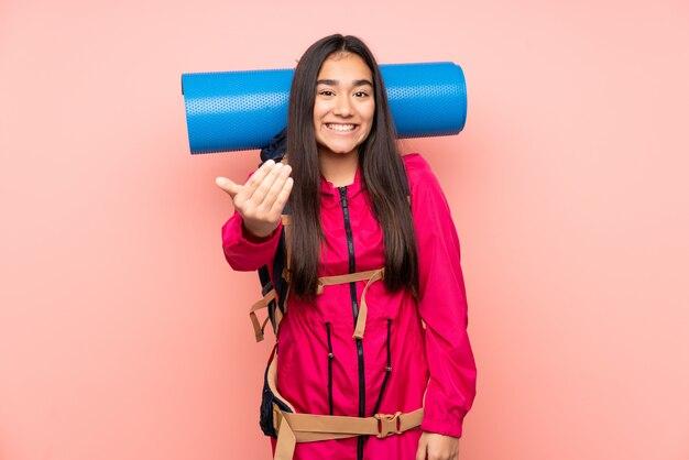 ピンクの壁に大きなバックパックを持つ若い登山家インドの女の子