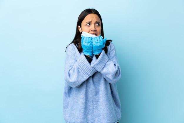 Молодая брюнетка смешанной расы защищает женщину с помощью маски и перчаток над голубой стеной